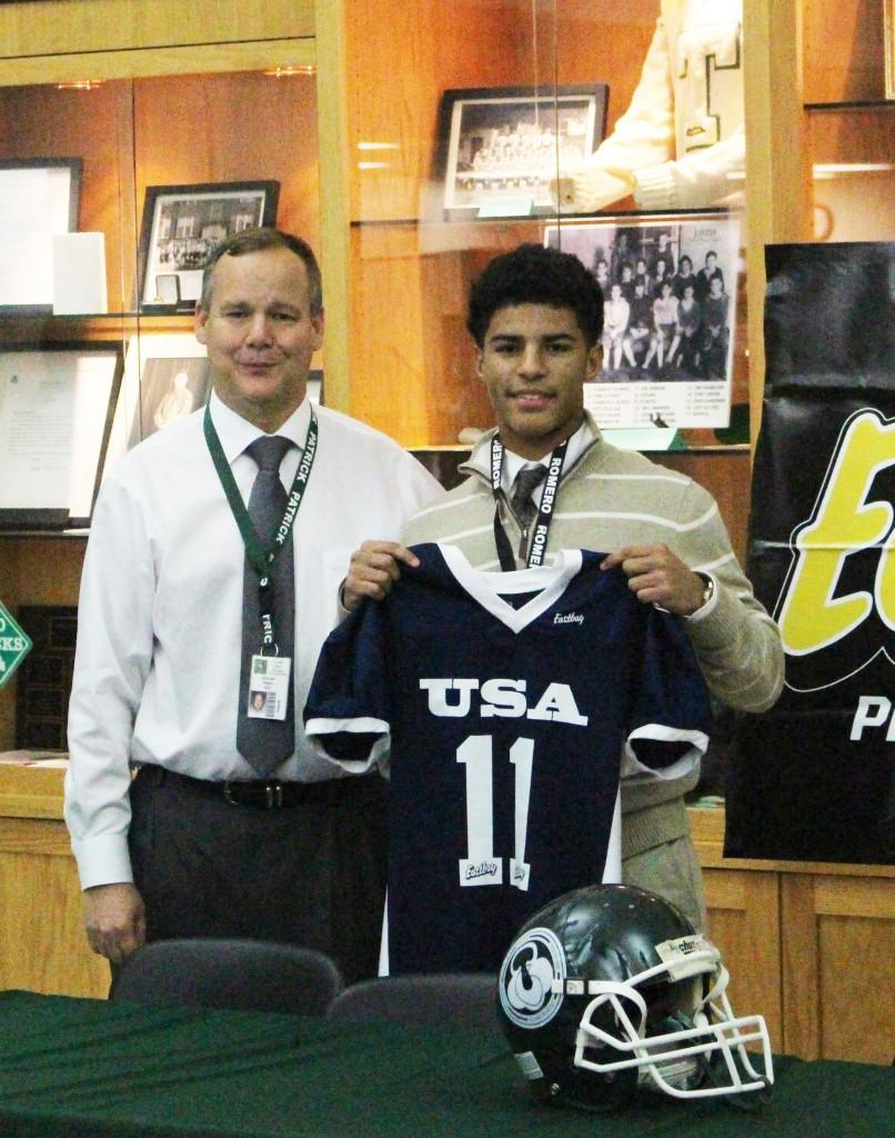 Trinity freshman football team quarterback Larry Harper was honored in a ceremony after school Dec. 11 in Alumni Hall. Harper was honored by Football University as an All-American freshman player.  Trinity freshman football team head coach Mike Magre is at left.                                -- photo by Devon Little