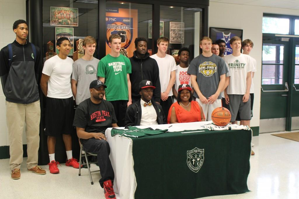 Senior Tre Ivory, seated at the table, is surrounded by relatives and teammates as he commits to play basketball at Austin Peay.